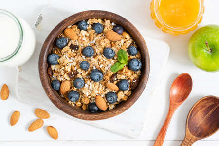 Homemade granola with nuts and berries in wooden bowl. Top view. Healthy breakfast, healthy eating, dieting and fitness food concept