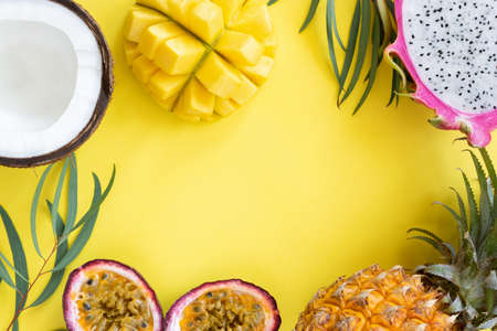 Tropical fruits mango, pitayam coconut and passion fruit on yellow background. Frame of resh fruits. Healthy lifestyle and summer concept Stock Photo