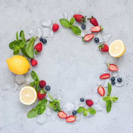 Frame of fresh berries, mint and ice on concrete background with copy space for text, top view. Concept of summer, freshness, ice cream, cocktail and summer desserts
