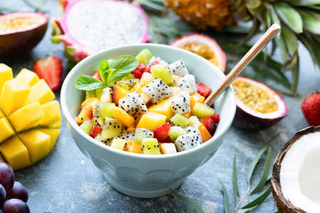 Fruit salad with tropical fruits mango, coconut, pitaya in a bowl. Thai summer holiday vegan food. Concept of healthy lifestyle, healthy eating, vegetarian diet