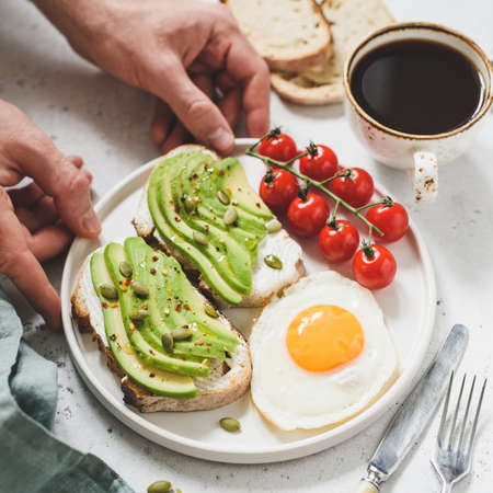 Toast with avocado, fried egg, tomatoes and cup of coffee. Healthy breakfast. Hands holding plate with healthy breakfast food. Concept of healthy lifestyle