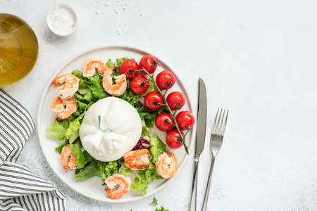 Healthy salad with burrata, shrimps, tomato and lettuce on white plate. Top view of tasty italian salad with olive oil dressing. Healthy eating concept Stock Photo