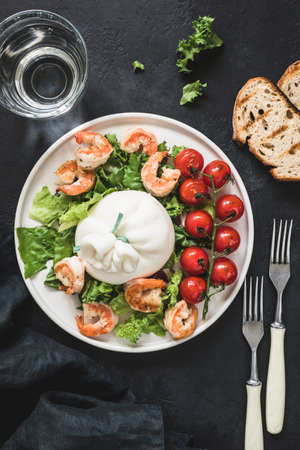 Salad with burrata cheese, shrimps, lettuce and tomatoes on white plate over dark background. Table top view. Healthy italian salad on plate Stock Photo