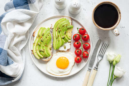 Breakfast avocado toast with fried egg, cherry tomatoes, cup of coffee and white flowers. Breakfast in bed. Healthy lifestyle, healthy eating concept