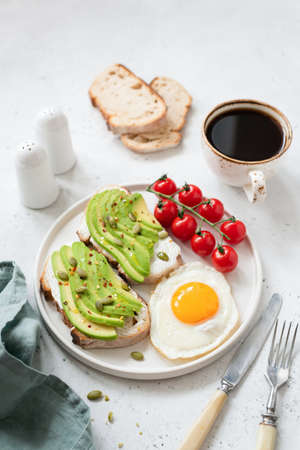 Toast with avocado, fried egg, tomatoes and coffee. Healthy breakfast on white concrete background. Selective focus. Healthy lifestyle concept