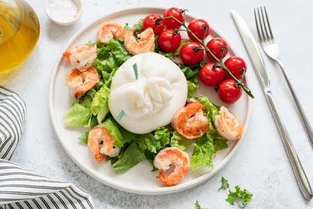 Burrata salad with shrimps, lettuce, tomatoes and olive oil on a white plate. Closeup view. Healthy italian salad Stock Photo