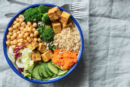 Salad bowl with quinoa, tofu, chickpeas and vegetables on linen textile background. Top view, copy space for text Stock Photo