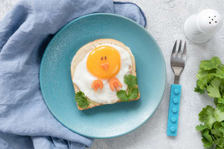 Creative food art breakfast idea for kids. Chicken shaped toast on a blue plate, meal for kids. Children breakfast, top view