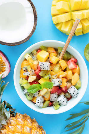 Healthy fruit salad with mango, pineapple, peach and pitaya on bright blue background. Top view. Tropical fruit salad. Thai food Stock Photo