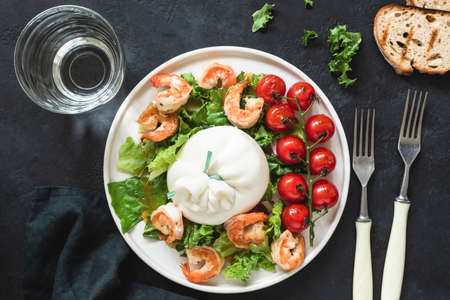 Salad with burrata cheese, shrimps, lettuce and tomatoes. Table top view. Salad on dark background. Healthy italian salad