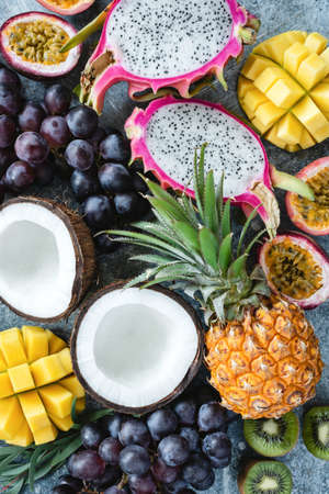 Exotic or tropical fruits assortment. Pineapple, coconut, passion fruit, pitaya, grapes and kiwi. Group of fresh fruits. Fruit background