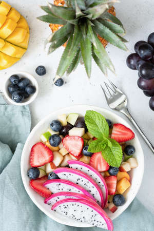 Fruit salad with tropical fruits in a bowl. Table top view