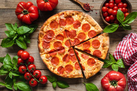 Pepperoni pizza, tomatoes and basil. Tasty pepperoni pizza on rustic wooden background. Overhead view of italian pizza