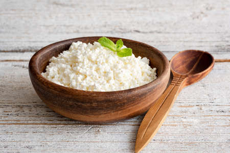Ricotta cheese, curd cheese, farmers cheese or tvorog in wooden bowl. Selective focus. Concept of healthy eating, healthy lifestyle and dieting