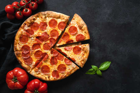 Pepperoni pizza on black concrete background. Top view with copy space. Tasty sliced pepperoni pizza Stock Photo