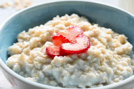 Oatmeal porridge with strawberries closeup view