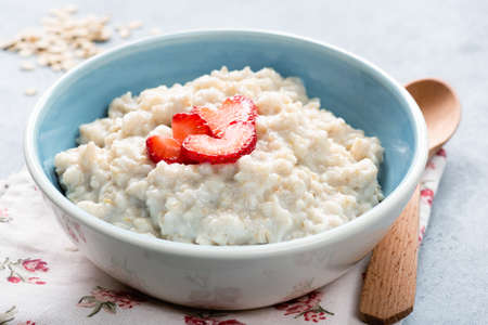 Oatmeal porridge with strawberries in a bowl. Oats porridge bowl. Healthy eating, healthy lifestyle, dieting concept