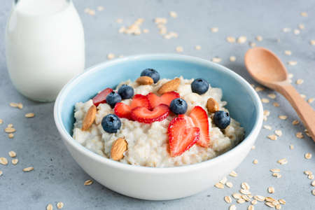 Oatmeal porridge in a blue bowl with berries and nuts. Porridge oats bowl with strawberries blueberries and almonds. Healthy eating, dieting, vegetarian food concept