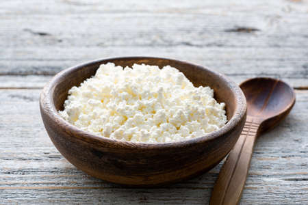 Ricotta cheese, cottage cheese farmers cheese, curd or tvorog in a wooden bowl. Closeup view, selective focus
