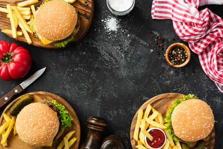 Burgers and french fries on dark stone background, top view with copy space. Homemade hamburgers and fries. Fast food or BBQ concept Stock Photo