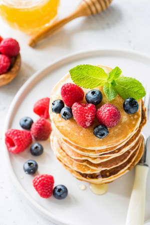 Pancakes with fresh berries and honey on white plate. Top view, selective focus Stock Photo