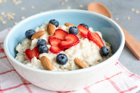 Hot oatmeal porridge with fresh berries and nuts in a blue bowl, closeup view. Concept of healthy eating, healthy lifestyle, dieting and fitness food