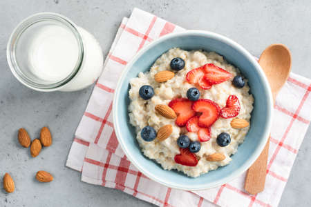 Oatmeal porridge with fresh berries and nuts in a bowl top view. Healthy lifestyle, healthy eating, dieting, fitness and vegetarian food concept