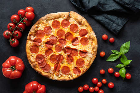 Hot pepperoni pizza on black stone background. Sliced tasty pizza with salami, cheese and tomatoes on dark table, top view