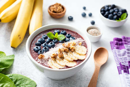 Acai smoothie bowl topped with banana, chia seed, blueberries, walnuts and coconut. Concept of healthy eating, healthy lifestyle, dieting, detox and vegan food
