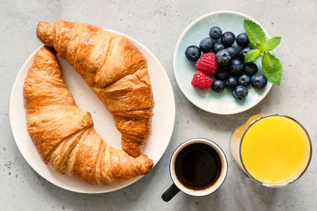 Croissant, black coffee, orange juice and fresh berries blueberry raspberry on concrete background. Top view. Breakfast, brunch, coffee break or snack concept Banque d'images - 104679277