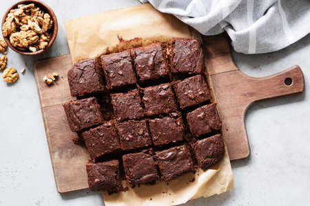 Chocolate brownie squares with walnuts on cutting board, top view, horizontal composition. Flat lay food Фото со стока