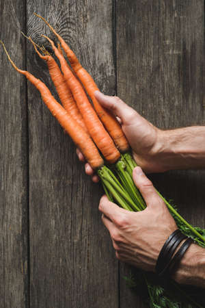 Carrots in farmers hands on wooden background. Agriculture, root vegetable harvest. Top view, vertical composition Фото со стока