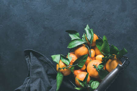 Mandarines or tangerines with leaves in basket on concrete background. Top view, copy space for text Фото со стока