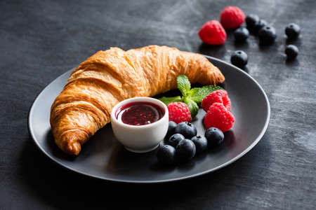 Croissant with fresh berries and jam on black plate. Sweet food, dessert concept