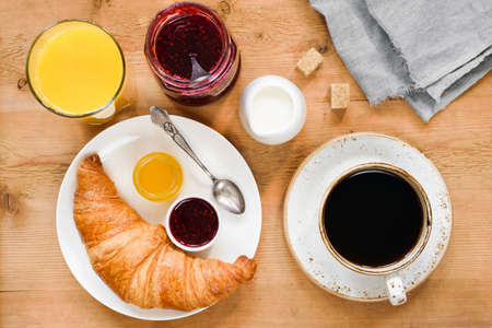 Croissant, cup of coffee, cream, orange juice, honey and jam on wooden table. Breakfast in cafe, hotel, continental breakfast or coffee break concept