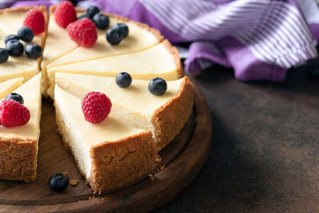 Classic plain New York Cheesecake with fresh berries sliced on wooden board, closeup view, selective focus