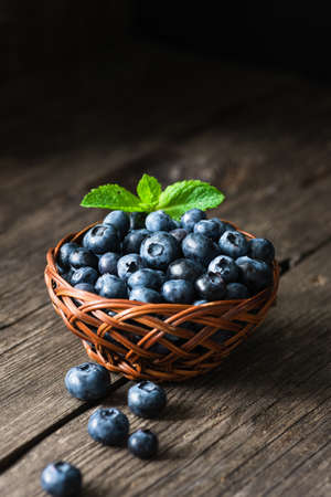 Blueberries in basket on wooden table. Freshly picked blueberries. Low key, dark food photo. Summer harvest. Selective focus Фото со стока