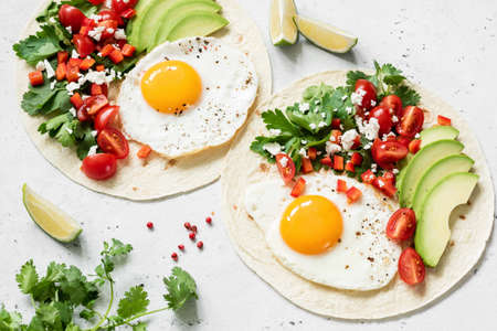 Flatbread tortilla with avocado, salsa and egg on concrete background. Healthy breakfast, lunch or dinner Фото со стока