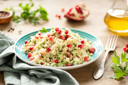 Tabbouleh, Middle Eastern couscous salad with pomegranate, parsley, cucumber on authentic turquoise plate. Vegetarian meal