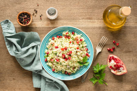 Vegetarian arabic couscous salad Tabbouleh with pomegranate seeds, parsley and olive oil. Top view Фото со стока