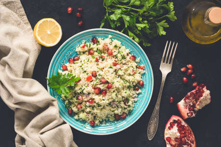 Middle Eastern Salad Tabbouleh With CousCous, Pomegranate seeds, Parsley. Top view, toned image Фото со стока