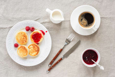 Cottage cheese pancakes with raspberry jam and coffee. Top view. Syrniki or sirniki, russian cuisine farmers cheese fritters or pancakes Фото со стока