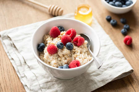 Oats porridge with fresh berries in a bowl, selective focus