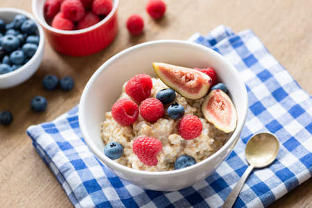 Oatmeal porridge with raspberries, blueberries and figs. Healthy breakfast food. Colofrul breakfast on a table