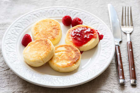 Cottage cheese pancakes or syrniki with jam on white plate. Sweet breakfast food. Russian or Ukrainian cuisine