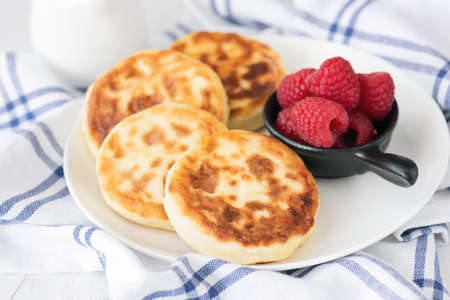 Cottage cheese pancakes on white plate. Also known as syrniki, sirniki or cottage cheese fritters. Russian cuisine
