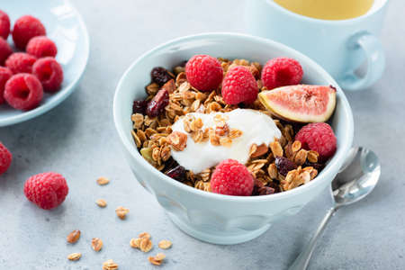 Granola with yogurt, berries and fruits in bowl. Healthy tasty breakfast with yogurt, homemade granola, fresh raspberries and figs. Cup of green tea on background
