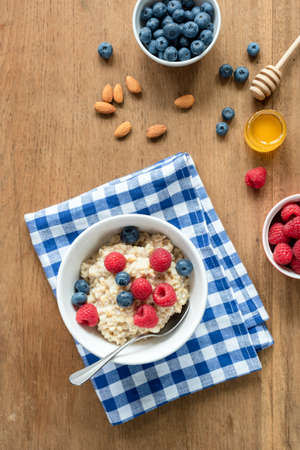 Breakfast table with oatmeal porridge, fresh berries and honey. Top view. Concept of healthy eating, healthy lifestyle Фото со стока