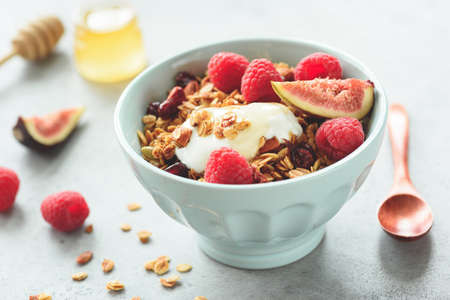 Healthy Breakfast or Snack Granola with Yogurt, Raspberries, Figs in a Bowl. Closeup view, toned image. Concept of healthy lifestyle, healthy eating, dieting, fitness menu Фото со стока