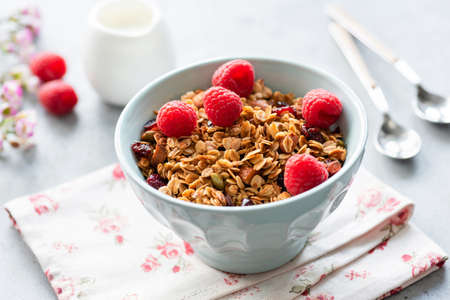 Granola with fresh raspberries in a bowl. Closeup view, selective focus. Homemade tasty granola. Concept of healthy eating, healthy lifestyle, recipe or fitness menu Фото со стока